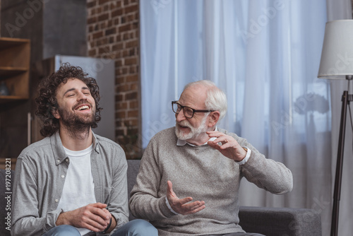 adult son and senior father talking and laughing at home