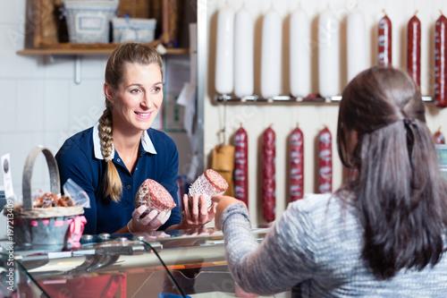 Cuadros en Lienzo  Verkäuferin in der Fleischerei bedient Kundin