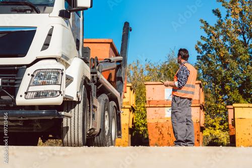 Fotografía  Bauarbeiter auf Baustelle lädt Bauschuttcontainer ab