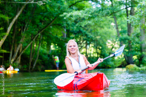 Photo Woman paddling with canoe on forest river in summer