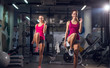 Leinwanddruck Bild - Portrait view of two young happy motivated attractive healthy sporty active slim girls doing exercises and warming with one raised leg in the gym.