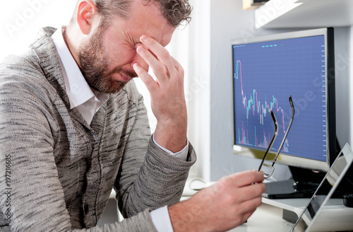 Fotografía  Depressed investor analyzing crisis stock market with graph on screen at home of