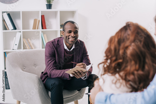 Fotografie, Obraz  Smiling african american psychiatrist talking to young couple