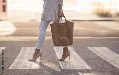 Fotografia  close up of woman legs walking on crosswalk