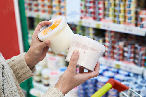Fotoposter Zuivelproducten Buyer hands with plastic yogurt jars at grocery