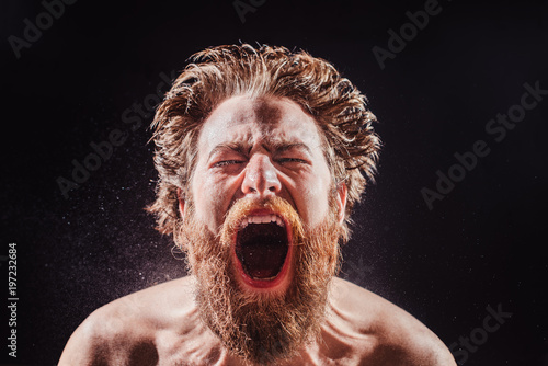 Cuadros en Lienzo A bearded man shouts in a spray of water against a black background