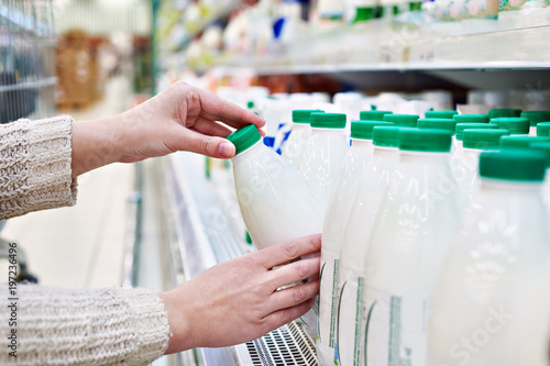 Woman takes bottle of milk from shelf in grocery