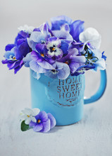 Photo Of A Beautiful Purple Pansy Flowers Close-up In A Blue Mug On A Light Background. Beautiful And Delicate Flowers.