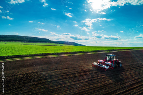 Fotografía  Aerial view of tractors working on the harvest field
