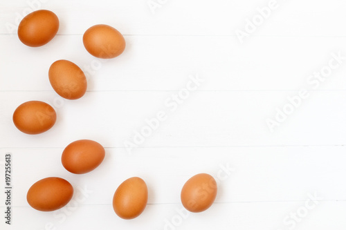Fotografía fresh or raw brown eggs on white wooden background, top view, flat lay with copy