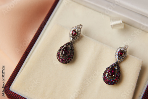 Photo Pair of ruby diamond earrings with red ruby stone on a silk peach background
