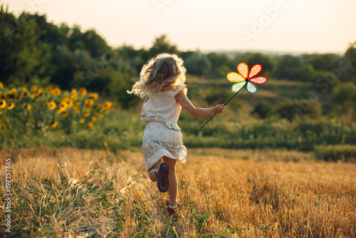 Obraz Cute little girl playing in the summer field of wheat - fototapety do salonu