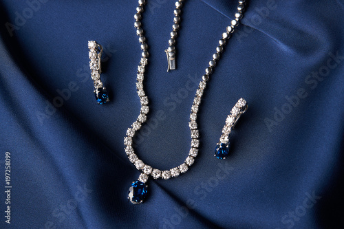Fotografija Women's platinum necklace and earrings with a diamond and blue precious sapphire stone on a silk blue background, close-up