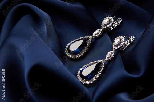 Fényképezés Pair of platinum earring with sapphire on blue satin background