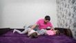 Father is tickling his two kids on bed. Family is having fun. Girl is protecting oneself. She is laughing. Boy is looking at father. Main colors are white, pink, purple, gray and black.