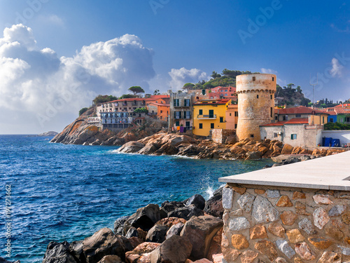 Cuadros en Lienzo Perfect tiny seaside village of Giglio Porto with multi colored houses, an ancient defensive tower and a rocky coastline against a deep blue Mediterranean sea