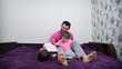 Father and his two kids are playing on bed. Family is having fun. Girl is lying on one side. Father and the boy are sitting, tickling her and laughing. Main colors are white, pink, purple, gray, black