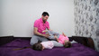 Family is having fun. Girl is lying belly down. Father is sitting and tickling his son. Boy is lying on one side and laughing. Main colors are white, pink, purple, gray and black.