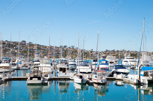 Many boats at San Diego California marina district with the hills of Point Loma in the background
