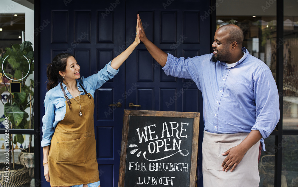 Fototapety, obrazy: Cheerful business owners standing with open blackboard