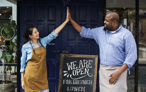 Fotografie, Obraz  Cheerful business owners standing with open blackboard