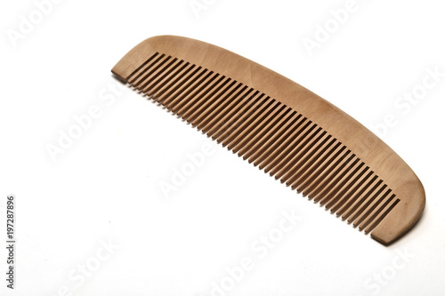 Fotografía closeup brown wooden comb on a white background