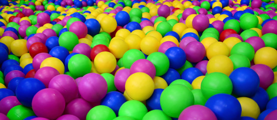 Mnogo šarenih plastičnih kuglica u dječjoj klupi na igralištu. Uzorak izbliza