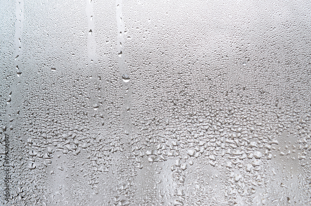 Fototapeta Texture of a drop of rain on a glass wet transparent background. Toned in grey color