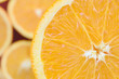 Top view of a fragment of the orange fruit slice on the background of many blurred orange slices. A saturated citrus texture image