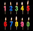 canvas print picture - Burning candles in the form of figures (numbers, dates) for cake isolated on black background. The concept of celebrating a birthday, anniversary, important date, holiday, table setting