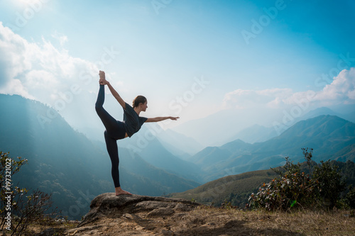 Woman training yoga, mountains on background