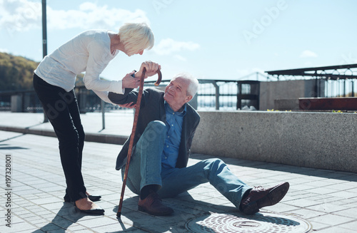 Obraz Let me help you. Loving wife giving her husband to lean on her after falling to the ground during a daily promenade. - fototapety do salonu