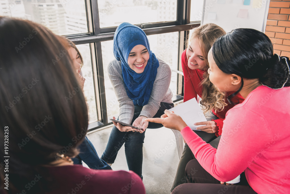 Fototapeta Women sitting in circle enjoying sharing stories in group meeting