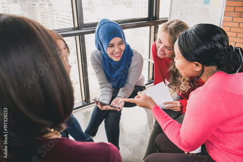 Women sitting in circle enjoying sharing stories in group meeting Fototapet
