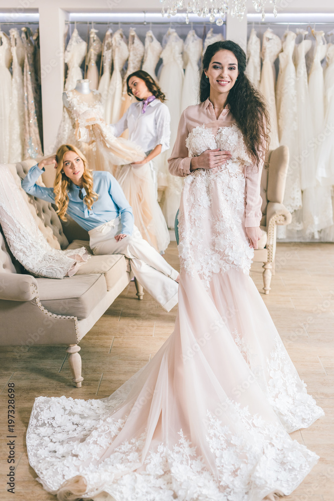 Wedding Atelier | Young Bride And Bridesmaids Holding Dresses In Wedding Atelier Foto