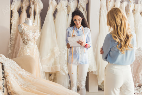 Photo Professional needlewoman holding clipboard with blonde woman in wedding atelier