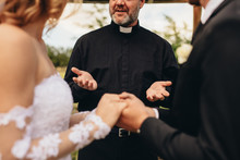 Priest Giving Blessings To Bride And Groom