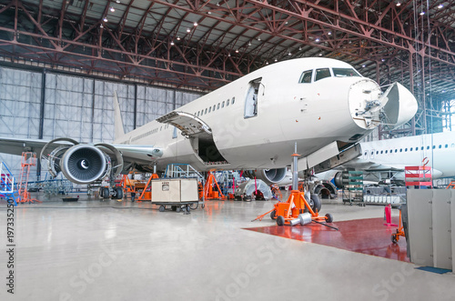 Türaufkleber Flugzeug Passenger airplane on maintenance of engine and fuselage repair in airport hangar. Aircraft with open hood on the nose and engines, as well as the luggage compartment.