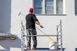 Imbianchino dipinge di bianco una facciata di uno stabile