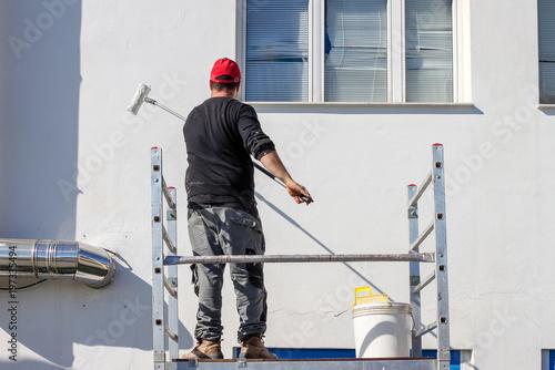 Fotografía  Imbianchino dipinge di bianco  una facciata di uno stabile
