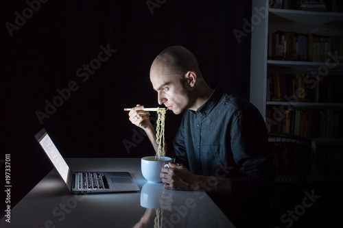Valokuvatapetti Young male at laptop computer eats instant ramen noodles late in the evening