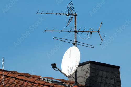 Satellitenschüssel und alte Antenne auf einem roten Dach Tablou Canvas