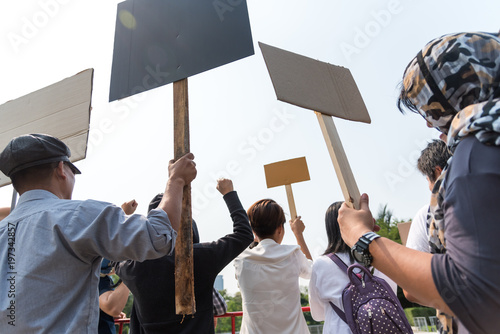 Fototapeta Men and women share a protest sign  hold a megaphone. Mob concept, The youth crowd gathered to protest. obraz