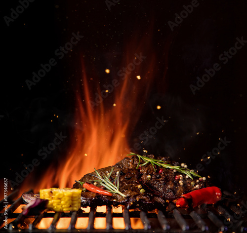 Fotografie, Obraz  Fiery grill grid with piece of beef steak and grilled vegetable.