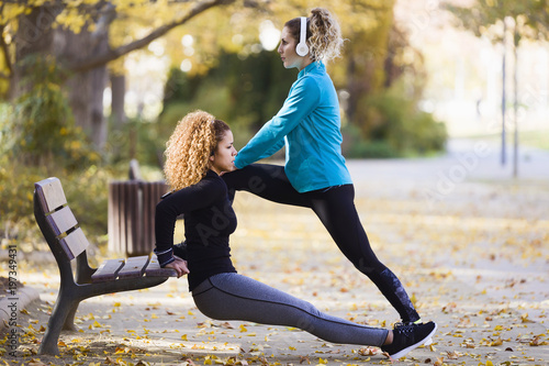 Two sportive young women stretching in park