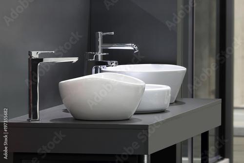 Fototapeta Umywalki z nowoczesnymi kranami na szarej szafce w łazience i w sklepie, trzy umywalki. obraz