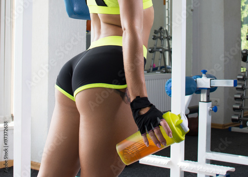 Active sexy woman in a sport green clothes stands at a sports gym equipment Fototapeta