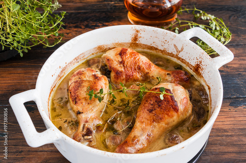 Keuken foto achterwand Kip Baked chicken drumsticks in a white casserole. Cooked in mustard sauce with mushrooms and thyme. Wooden rustic table.