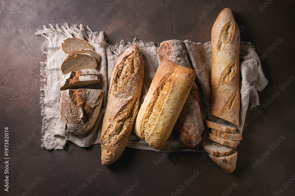 Variety of loafs fresh baked artisan rye, white and whole grain bread on linen cloth over dark brown texture background. Top view, copy space.