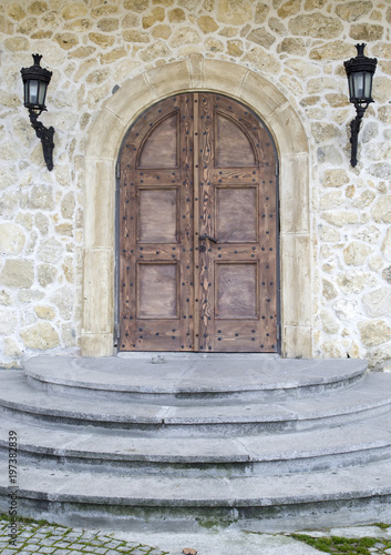 Fototapety, obrazy: Wooden door with arch on stone wall